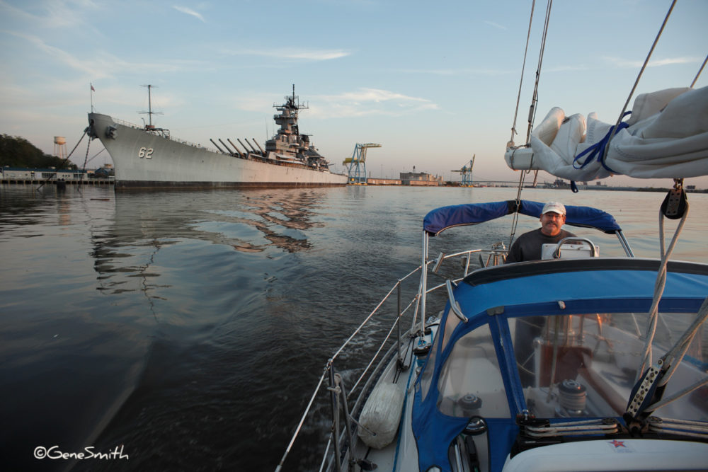 Yacht captain guides sailboat past Battleship New Jersey.