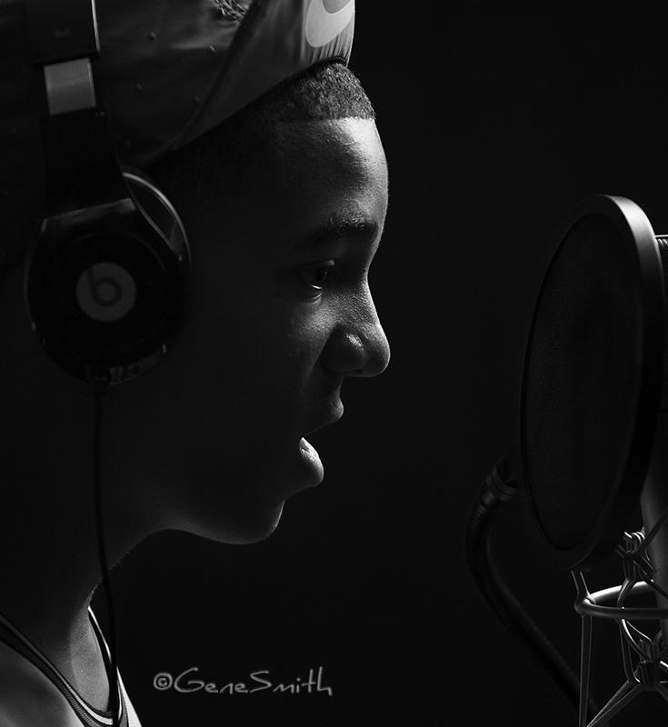 musician sings into mic in recording studio