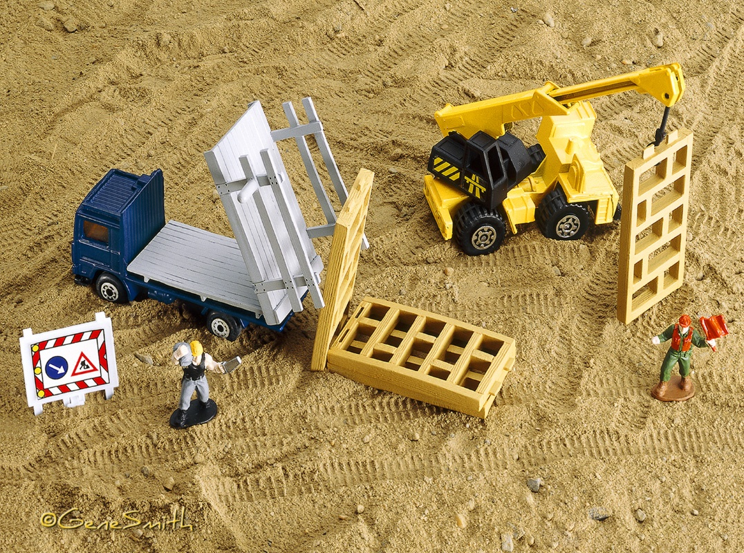 Matchbox construction toys in a play-setting with tiny tire tracks and little toy construction workers photographed by Gene Smith Studio for MATTEL Matchbox package design illustration.