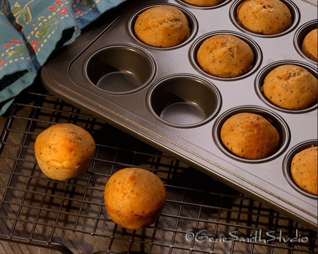 Home made muffins cool on rack next to pan