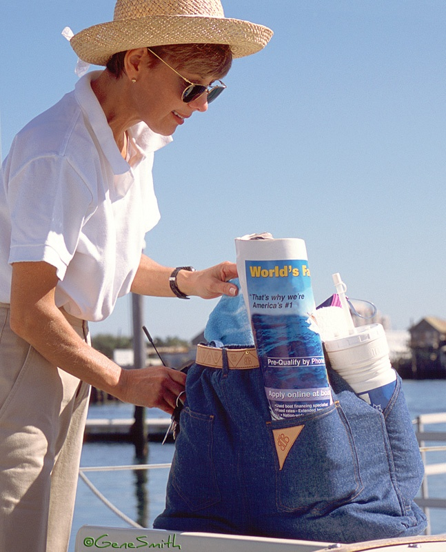 Attractive woman organizes items in her carry bag at marina before getting underway on sailboat