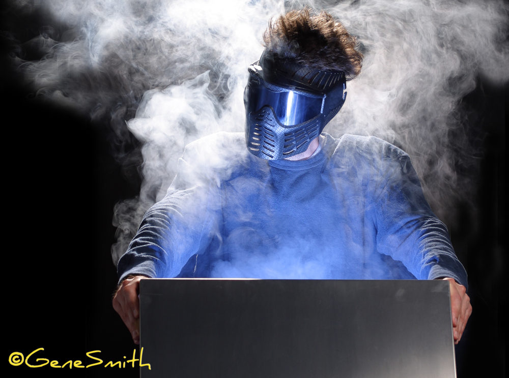 Man dressed in blue with sports helmet and goggles opens mystery case to reveal smokey surprise.