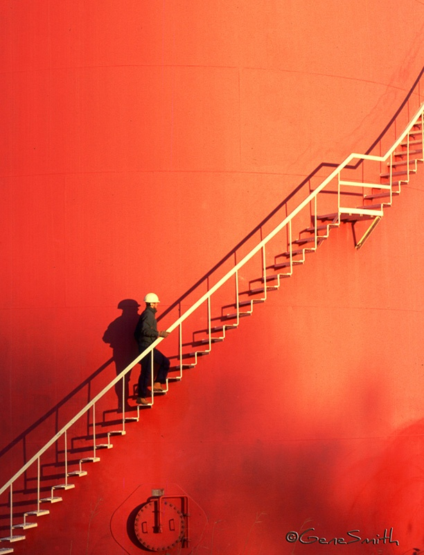 man climbs orange water tower