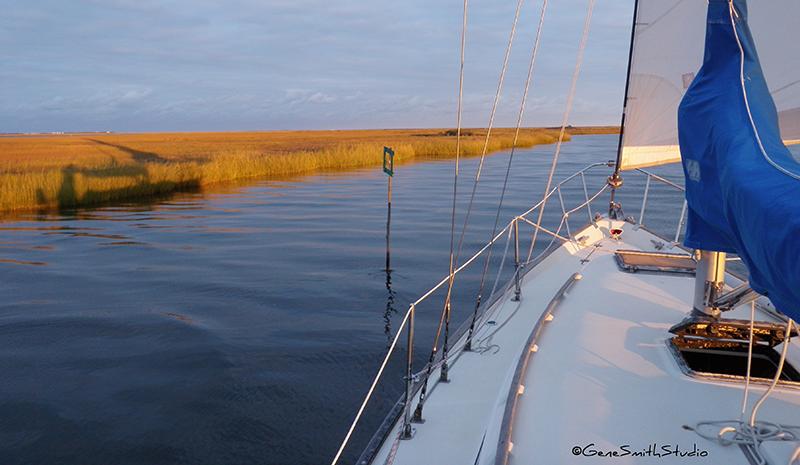 yacht glides up tidal creek next to sawgrass