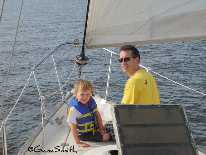 father and son enjoy bow of sailboat on gentle reach sail.