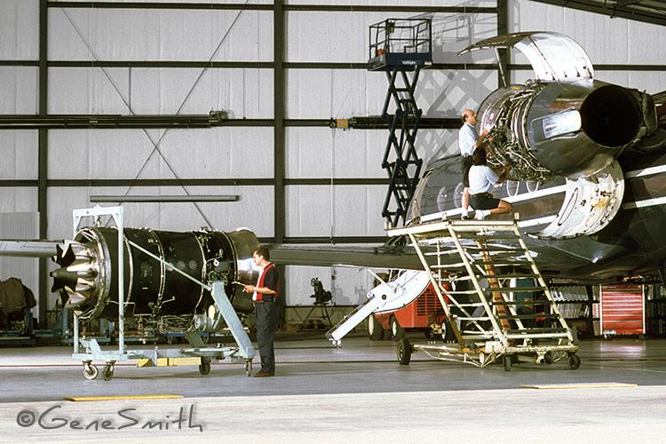 Technicians service Rolls Royce Jet Airplane engines in big hanger