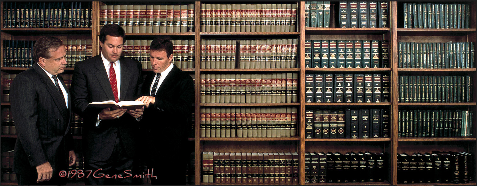 insurance executives photographed in front of books