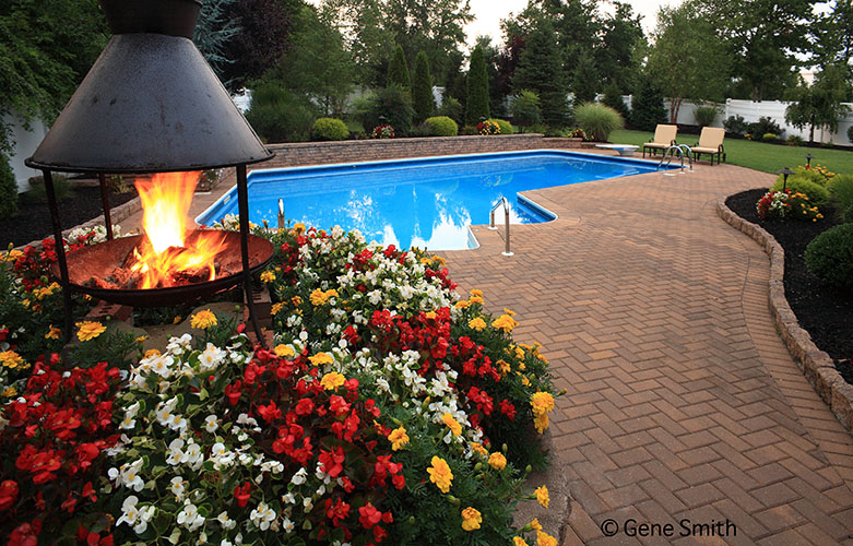 swimming pool and patio with built in gas fire pit