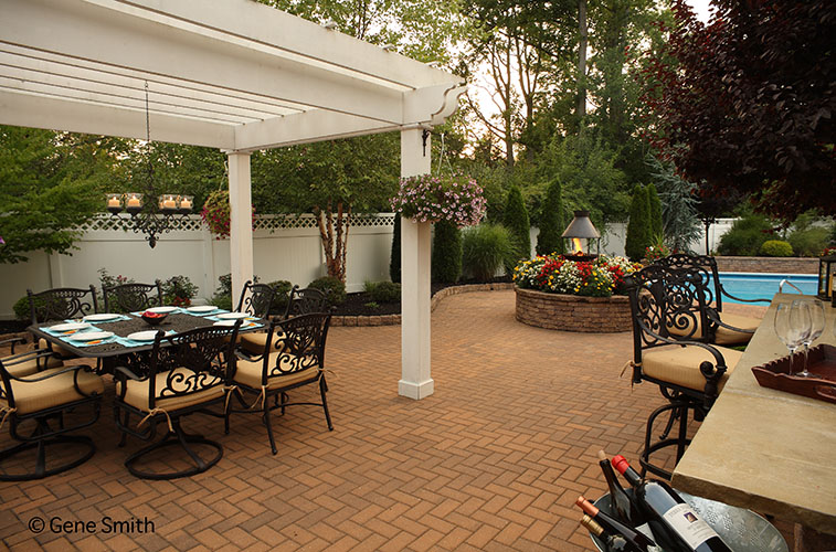 Brick patio and gazebo surround pool and outdoor bar and fire pit.