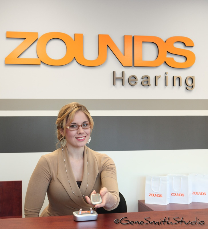 Attractive saleswoman offers hearing aid equipment.