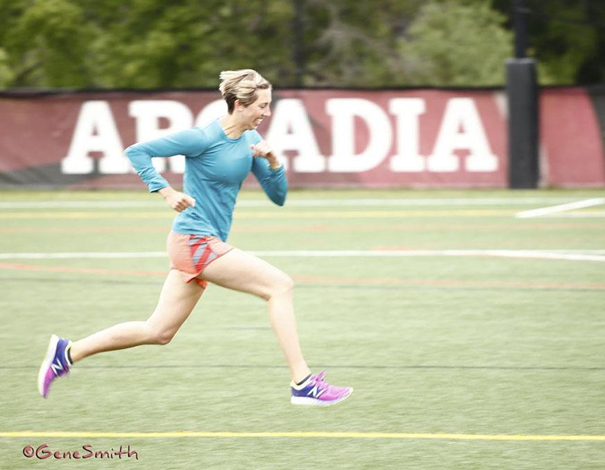 Blonde female runner on university soccer field runs at full gait.