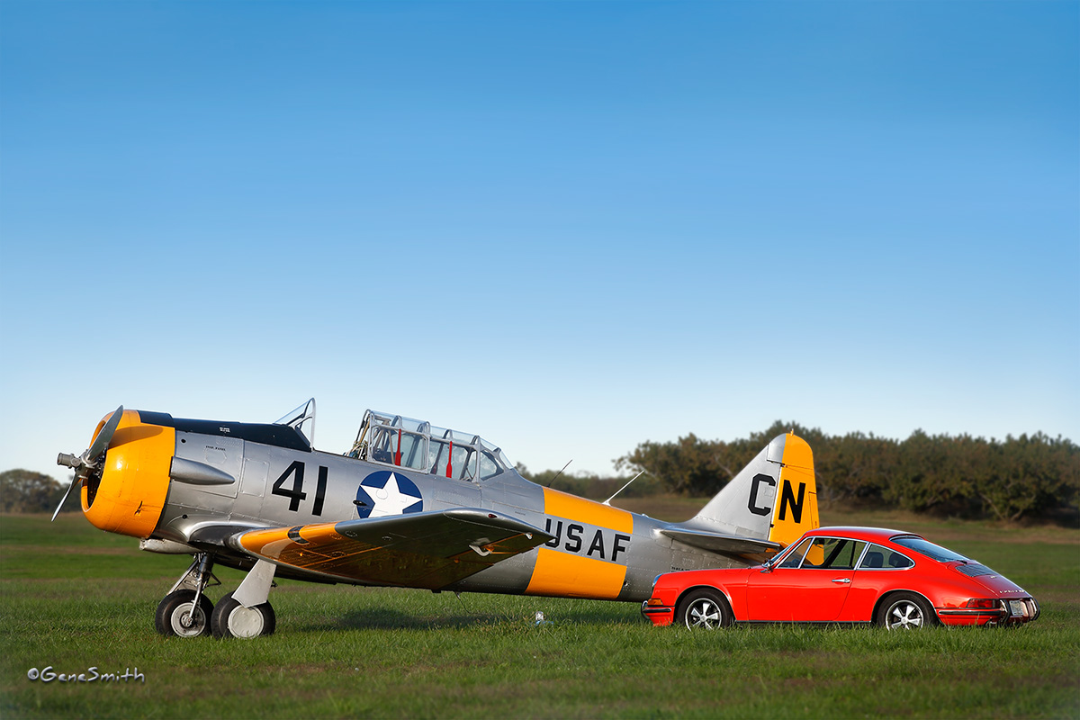 Vintage airplane trainer and 1969 PORSCHE 911S parked in airstrip field
