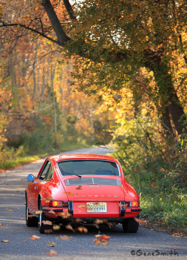 Orange Porsche 911S driving on country road in Fall.