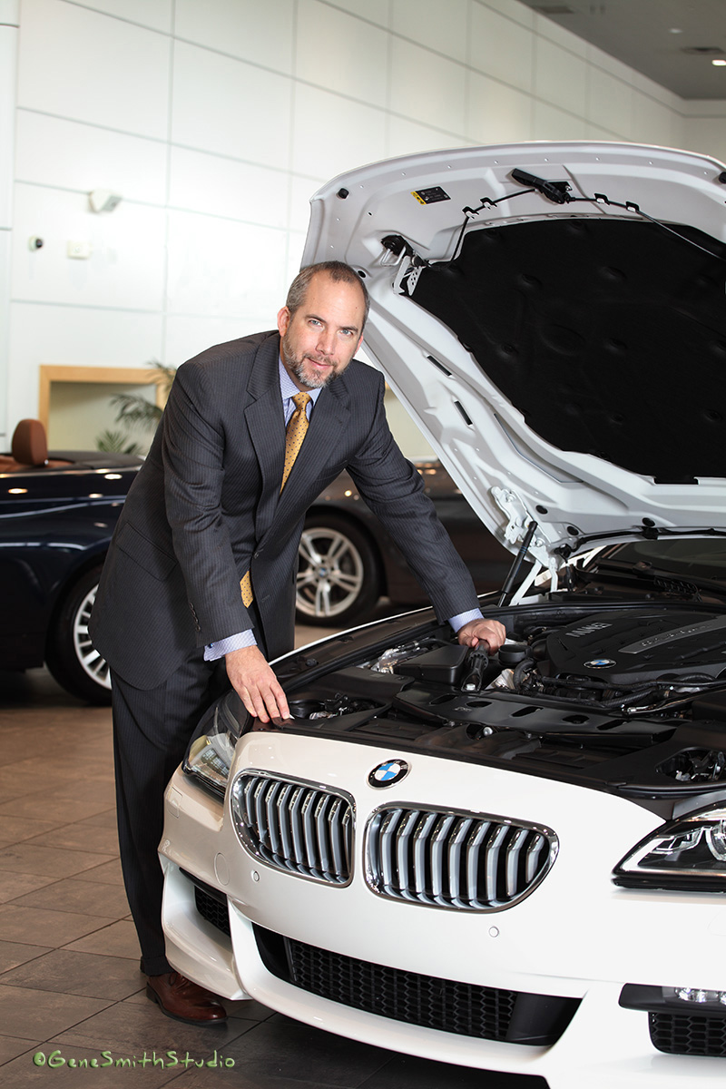 CEO in suit and tie photographed with white BMW in Holman Showroom.
