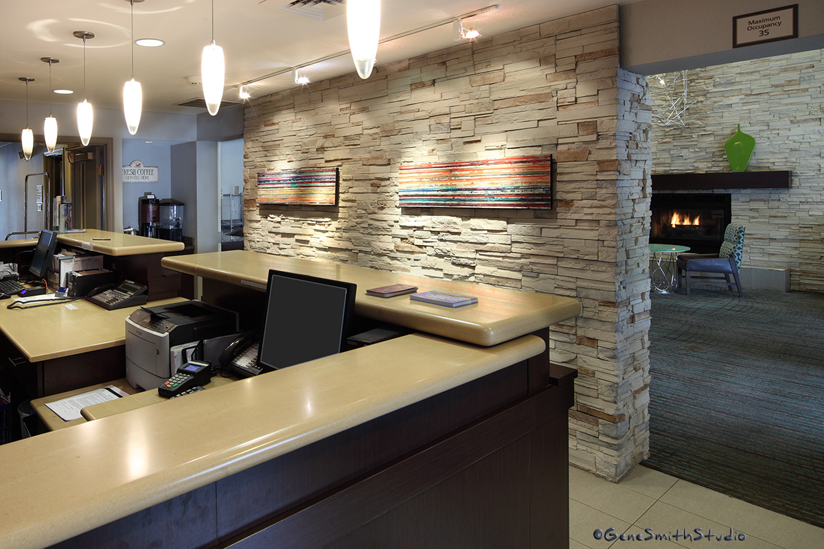 Hotel reception area and adjacent lounge with fireplace.