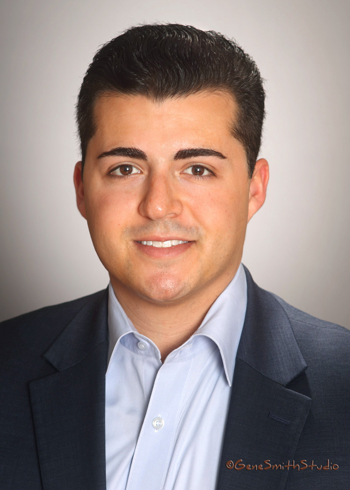 Sharp young man in jacket and dress shirt poses for facebook headshot