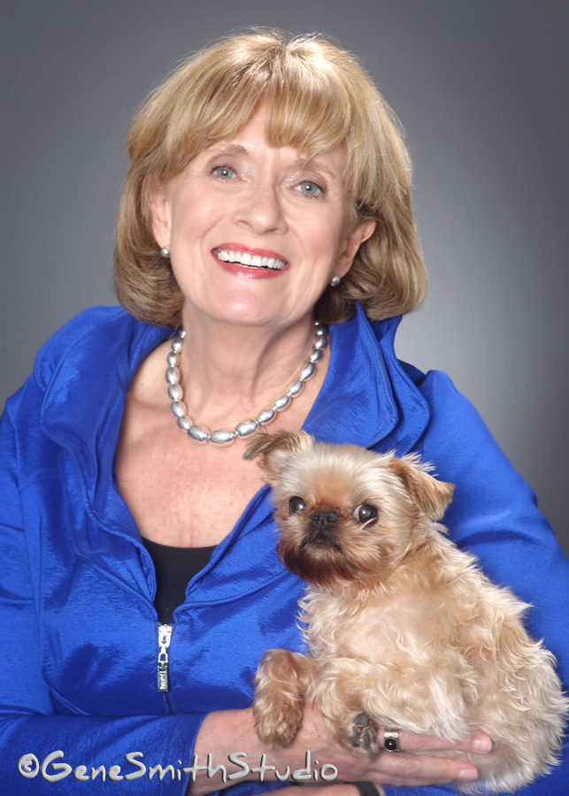 Blond female executive in blue jacket poses with her pet dog.