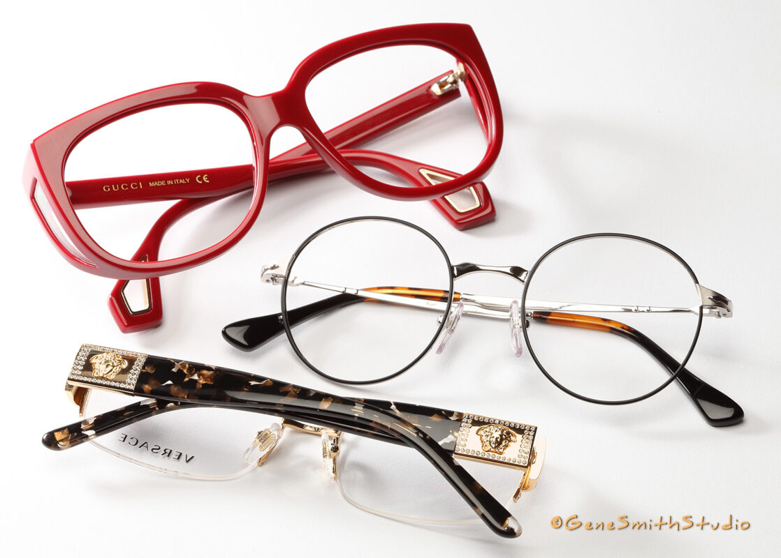 A professional photo for advertising by Gene Smith Studio, Commercial and Headshot Photographer in Cherry Hill, NJ of red GUCCI eyeglasses with luxury gold VERSACE and upscale round lens eyeglass frames.