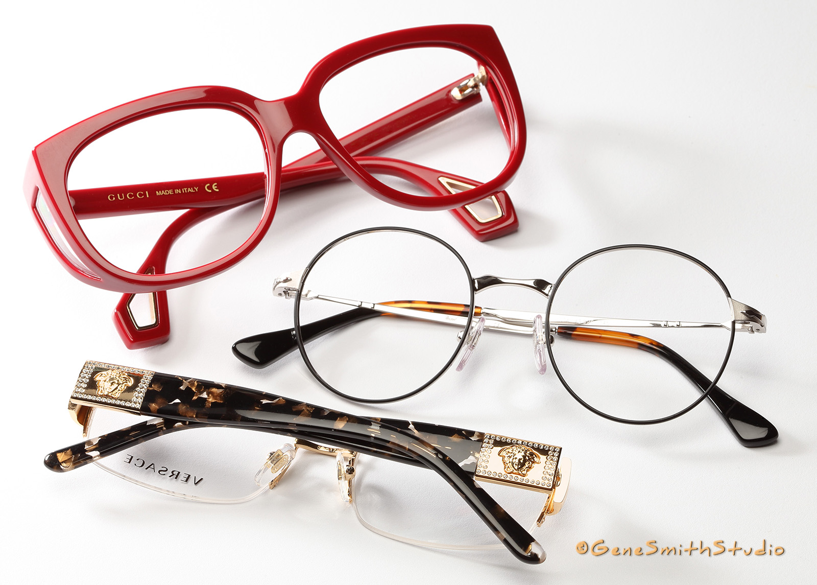 A professional photo for advertising by Gene Smith Studio, Commercial and Headshot Photographer in Cherry Hill , NJ of red GUCCI eyeglasses with luxury gold VERSACE and upscale round lens eyeglass frames.